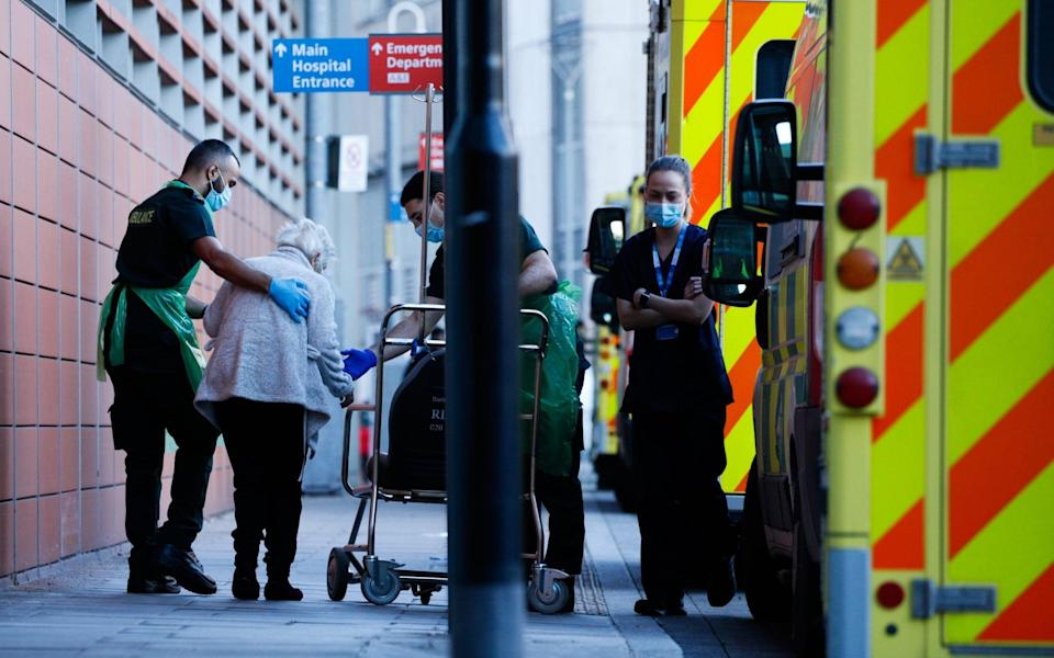 Paramedics help an elderly patient into a wheelchair outside the emergency department of the Royal London Hospital - David Cliff/Getty