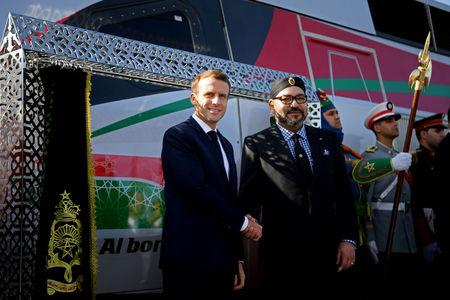 French President Emmanuel Macron and Moroccan King Mohammed VI shake hands as they inaugurate a high-speed line at Rabat train station
