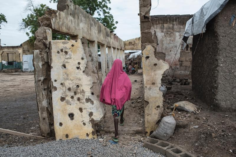A girl walks through an area where a Nigerian fighter jet mistakenly bombed civilians in January
