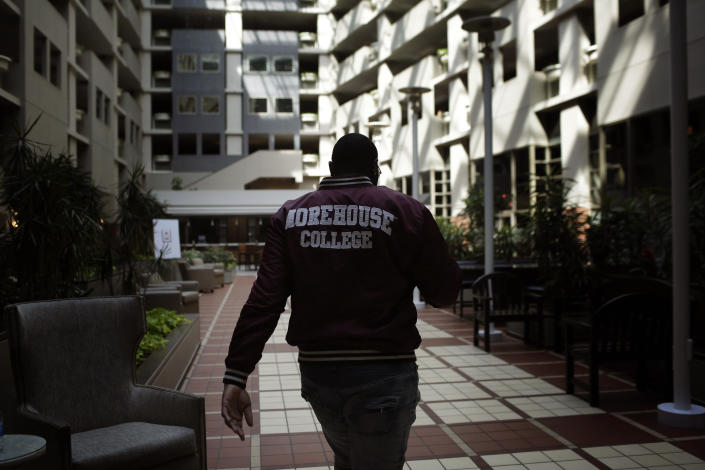 """In this Tuesday, May 5, 2020, photo, Morehouse College senior Lanarion """"LTL"""" Norwood Jr., of Atlanta, walks through a hotel lobby in Atlanta. Students were sent home from the college amid the new coronavirus outbreak. (AP Photo/Brynn Anderson)"""