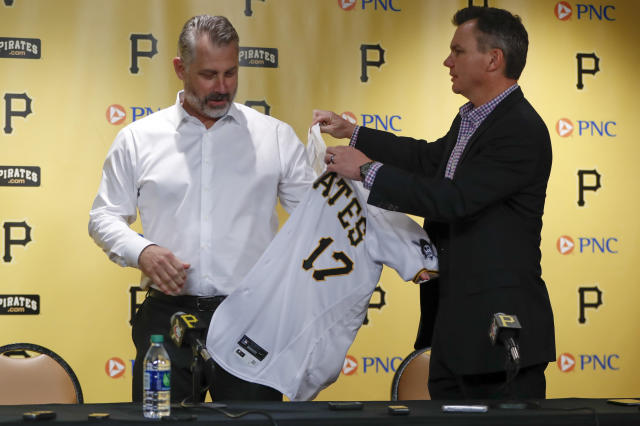Derek Shelton, left, is helped on with his uniform jersey by general manager Ben Cherington as he is introduced as the new manager of the Pittsburgh Pirates baseball team at a news conference, Wednesday, Dec. 4, 2019, in Pittsburgh. (AP Photo/Keith Srakocic)