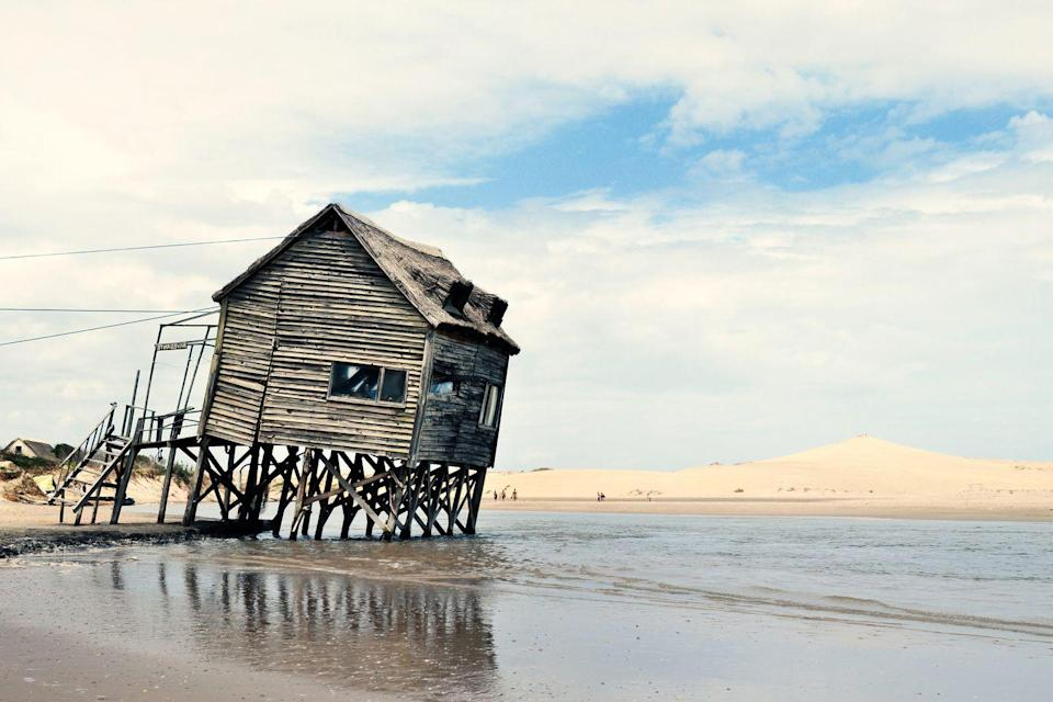 <p>Old wooden posts barely keep this former seaside getaway above water.</p>