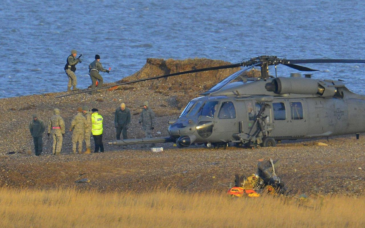 REFILE - CLARIFYING CAPTION   A Pave Hawk helicopter, military personnel and emergency services attend the scene of a helicopter crash on the coast near the village of Cley in Norfolk, eastern England January 8, 2014. British police said on Wednesday they would be working with the U.S. Air Force and others to find out why a U.S. military helicopter crashed on the coast of eastern England, killing all four crew on board. The helicopter, a Pave Hawk assigned to the 48th Fighter Wing based at RAF Lakenheath air base, was performing a low-level training mission along the Norfolk coast when it went down in marshland on Tuesday evening. The helicopter pictured is not the crashed helicopter but a second helicopter, which had been taking part in the same training exercise as the one that crashed. REUTERS/Toby Melville (BRITAIN - Tags: MILITARY DISASTER TPX IMAGES OF THE DAY)