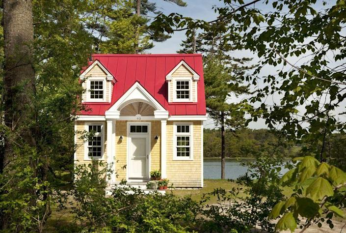 """<p>This darling red-roofed cottage sits in a grove of leafy trees near the water's edge in Freeport, Maine. Designed by Mac Lloyd of Creative Cottages, the environmentally sensitive abode packs in a full kitchen, bathroom, living space, sleeping quarters, gas fireplace, laundry, and a loft space, while still managing to seem airy and spacious. </p><p><a class=""""link rapid-noclick-resp"""" href=""""http://www.creativecottagesllc.com/"""" rel=""""nofollow noopener"""" target=""""_blank"""" data-ylk=""""slk:SEE INSIDE"""">SEE INSIDE</a></p>"""