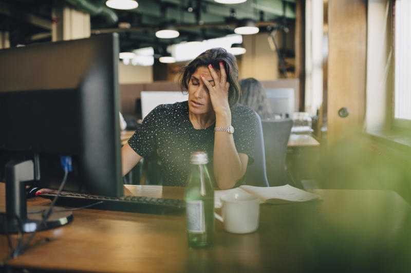 Tired businesswoman with head in hand sitting at computer desk in office