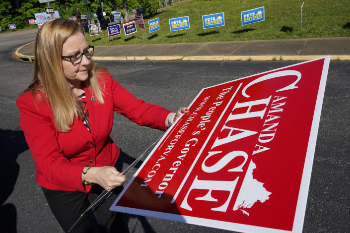 Republican gubernatorial candidate State Sen. Amanda Chase, assembles a yard sign during a drive through GOP Convention vote in Chesterfield, Va., Saturday, May 8, 2021. (AP Photo/Steve Helber)
