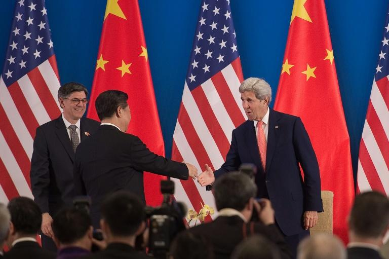 China's President Xi Jinping shakes hands with US Secretary of State John Kerry (R) as US Treasury Secretary Jacob Lew looks on during the opening session of the US - China Strategic and Economic Dialogues, in Beijing, on June 6, 2016