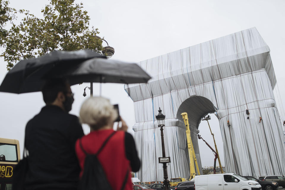 """People watch workers wrapping the Arc de Triomphe monument, Wednesday, Sept. 15, 2021 in Paris. The """"L'Arc de Triomphe, Wrapped"""" project by late artist Christo and Jeanne-Claude will be on view from, Sept. 18 to Oct. 3. The famed Paris monument will be wrapped in 25,000 square meters of fabric in silvery blue, and with 3,000 meters of red rope. (AP Photo/Lewis Joly)"""