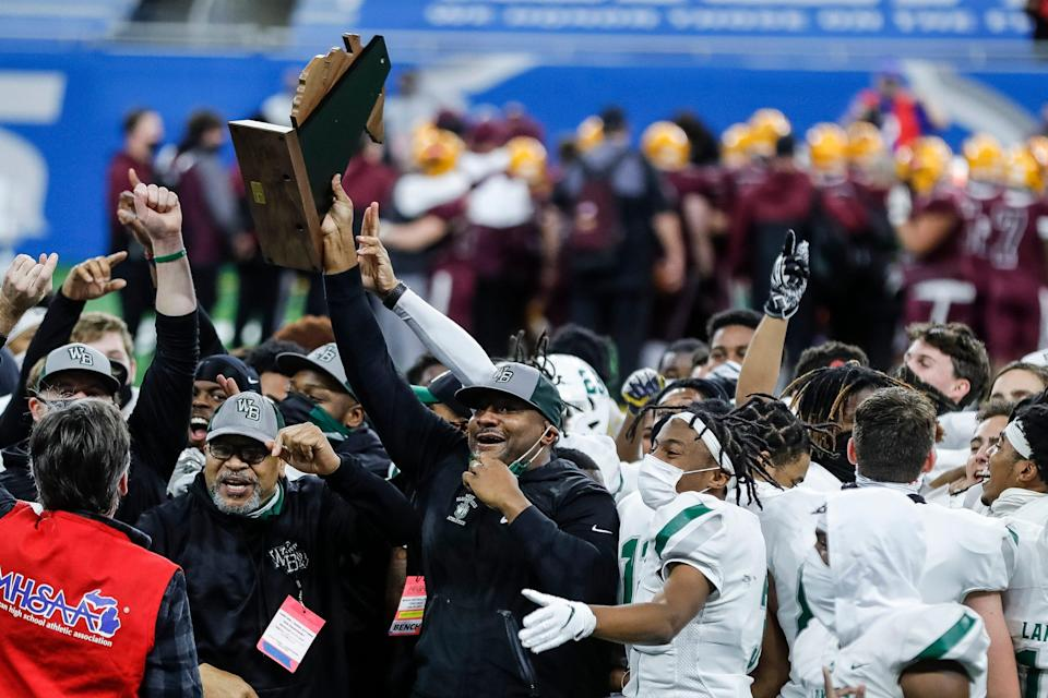 West Bloomfield head coach Ron Bellamy holds the trophy and celebrates with players and coaches after defeating Davison, 41-0, in the MHSAA Division 1 final at Ford Field, Saturday, Jan. 23, 2021.