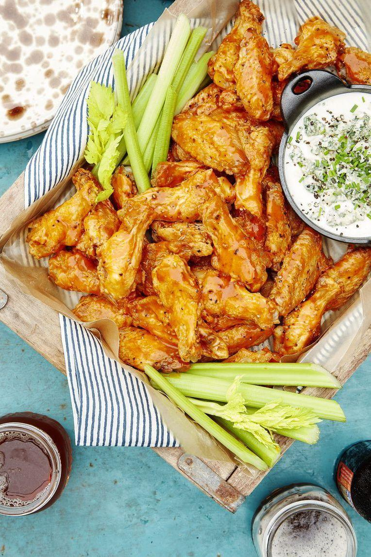 """<p>Nothing says perfect party food quite like wings. This is perfect for an appetizer or a whole meal — pair with some coleslaw or a summer salad, and you're good to go.</p><p><em><strong>Get the recipe at <a href=""""https://www.countryliving.com/food-drinks/a24398944/spicy-oven-baked-wings-with-blue-cheese-dip-recipe/"""" rel=""""nofollow noopener"""" target=""""_blank"""" data-ylk=""""slk:Country Living"""" class=""""link rapid-noclick-resp"""">Country Living</a>.</strong></em></p>"""