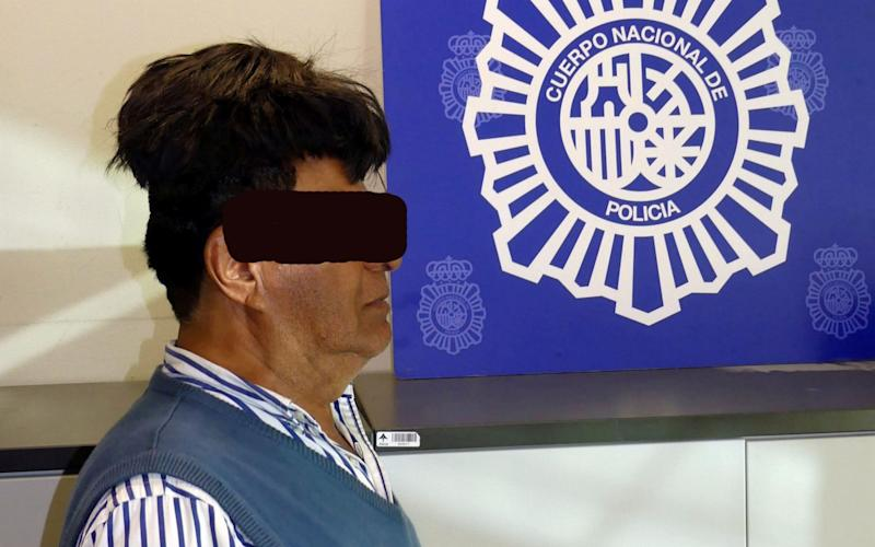 A man poses with a toupee with a drug package under it after being arrested in Barcelona - REUTERS
