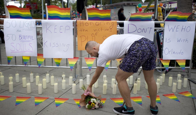 <p>Rickey Swanson arranges a bouquet of flowers at a memorial with 50 candles for at least 50 people gunned down at a gay nightclub in Orlando, Fla., during the Gay Pride Parade in West Hollywood, June 12, 2016. (Mindy Schauer/The Orange County Register via AP) </p>