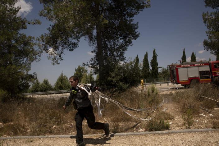 An Israeli first responder runs with hoses while battling wildfires for the second day near Shoresh, on the outskirts of Jerusalem, Monday, Aug. 16, 2021. Israel Fire and Rescue service said in a statement on Monday, that 45 firefighting teams accompanied by eight planes were working to contain five fires in the forested hills west of the city. (AP Photo/Maya Alleruzzo)