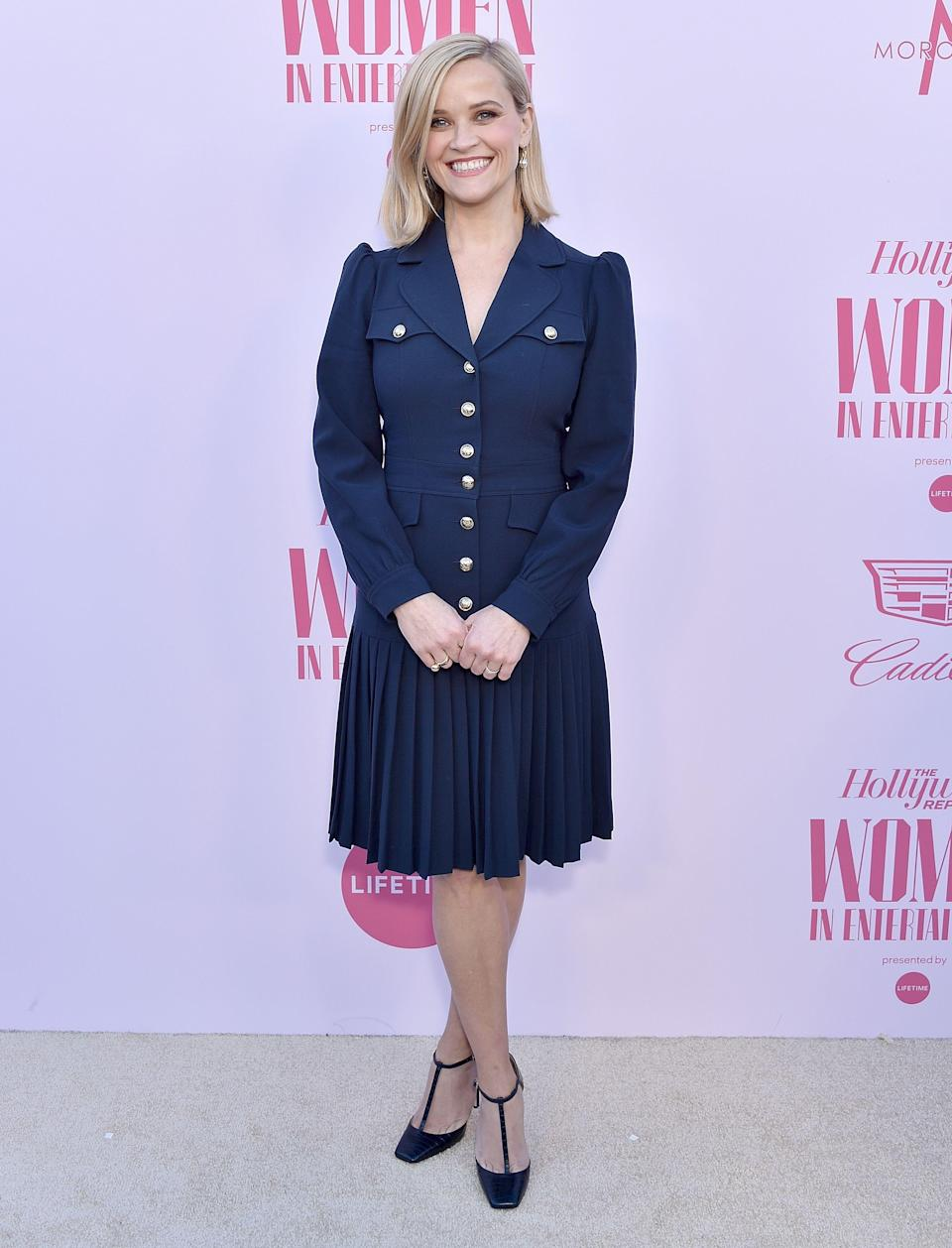 Reese Witherspoon stands on Women in Enterprise carpet wearing a professional navy blue dress