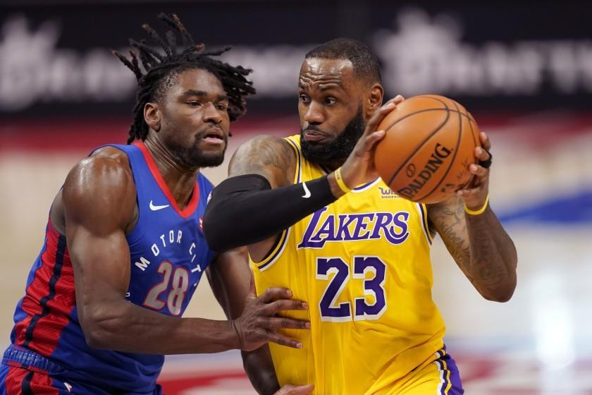 Los Angeles Lakers forward LeBron James (23) drives as Detroit Pistons center Isaiah Stewart (28) defends during the first half of an NBA basketball game, Thursday, January 28, 2021, in Detroit.  (AP Photo / Carlos Osorio)