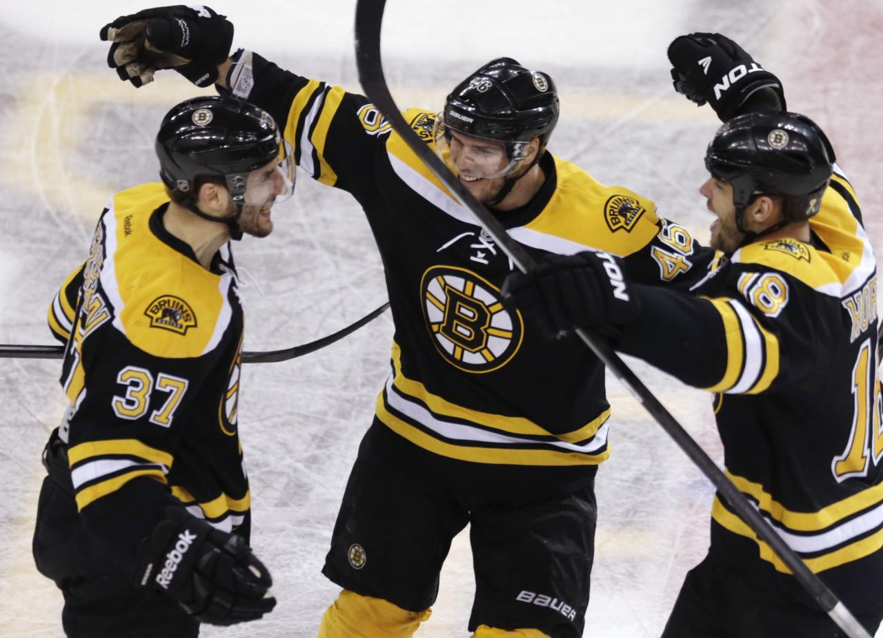 Boston Bruins center Patrice Bergeron, left, is congratulated by teammates David Krejci, center, and Nathan Horton, right, after his goal in the final minute of the third period, which tied the game 4-4 forcing overtime against the Toronto Maple Leafs, in Game 7 of their NHL hockey Stanley Cup playoff series in Boston, Monday, May 13, 2013. (AP Photo/Charles Krupa)