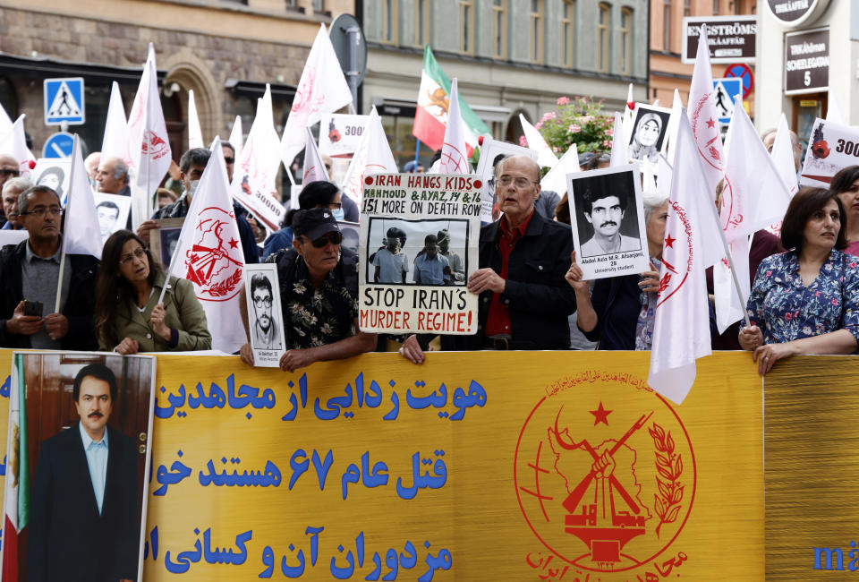 Supporters of the People's Mojahedin Organization of Iran protest outside Stockholm's district court on the first day of the trial of Hamid Noury, in Stockholm, Tuesday, Aug. 10, 2021. An Iranian man is standing trial in Sweden charged with grave war crimes and murder during the final phase of the Iran-Iraq war in the 1980s. The trial of Hamid Nouri comes just days after Iran's hard-line President Ebrahim Raisi took office as the highest-ranking civilian leader in the Islamic Republic. (Stefan Jerrevang/TT News Agency via AP)