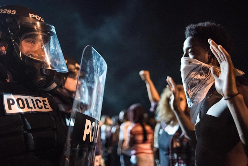 Police officers face off with protesters on the I-85 (Interstate 85) during protests in the early hours of September 21, 2016 in Charlotte, North Carolina. The protests began last night, following the fatal shooting of 43-year-old Keith Lamont Scott by a police officer at an apartment complex near UNC Charlotte. (Photo by Sean Rayford/Getty Images)