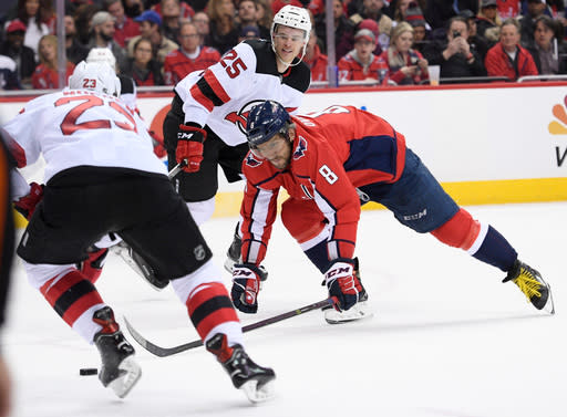 Washington Capitals left wing Alex Ovechkin (8), of Russia, chases the puck between New Jersey Devils right wing Stefan Noesen (23) and defenseman Mirco Mueller (25) during the second period of an NHL hockey game Saturday, April 7, 2018, in Washington. (AP Photo/Nick Wass)