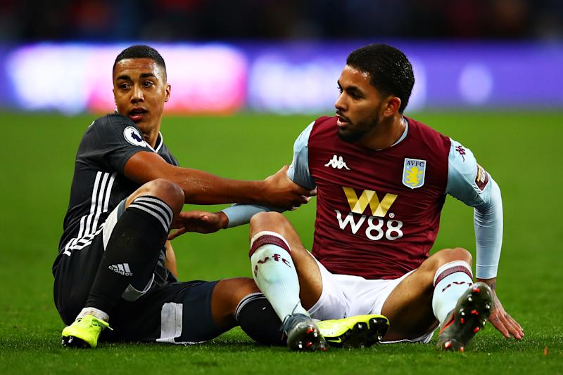 Youri Tielemans of Leicester City and Douglas Luiz of Aston Villa help each other up after a challenge during the Premier League match between Aston Villa and Leicester City at Villa Park on December 08, 2019 in Birmingham, United Kingdom.
