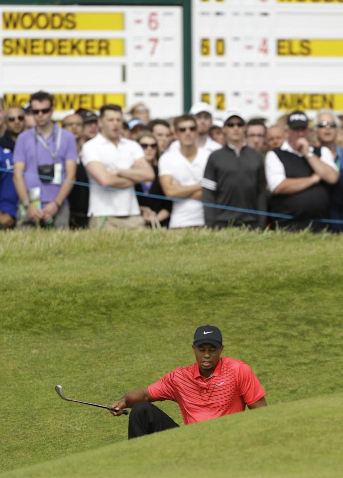 Tiger Woods of the United States slips in a bunker on the sixth hole at Royal Lytham & St Annes golf club during the final round of the British Open Golf Championship, Lytham St Annes, England Sunday, July 22, 2012. (AP Photo/Jon Super)