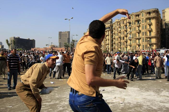 A protester throws a stone after scuffles broke out between groups of several hundred protesters in Tahrir square when chants against the new Islamist president angered some in the crowd in Cairo, Egypt, Friday, Oct. 12, 2012. The scuffles between supporters and opponents of President Mohammed Morsi reflect deep political divisions among the country's 82 million people, more than a year after the popular uprising that toppled Hosni Mubarak. (AP Photo/Khalil Hamra)