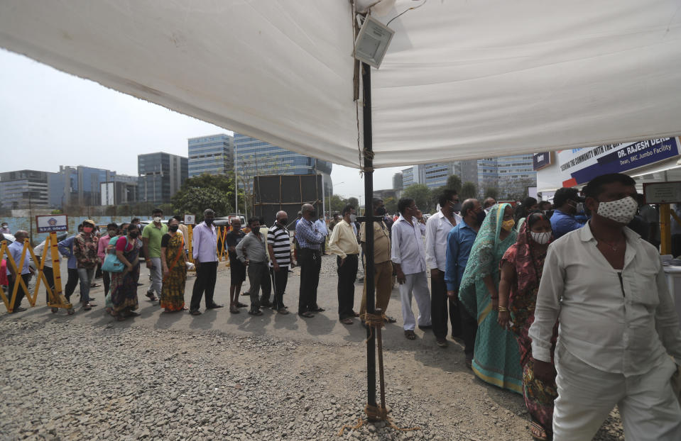 """People queue up for COVID-19 vaccine in Mumbai, India, Thursday, April 8, 2021. Nations around the world set new records Thursday for COVID-19 deaths and new coronavirus infections, and the disease surged even in some countries that have kept the virus in check. Indian Prime Minister Narendra Modi urged people to get vaccinated, writing in a tweet: """"Vaccination is among the few ways we have to defeat the virus. If you are eligible for the vaccine, get your shot soon."""" (AP Photo/Rafiq Maqbool)"""