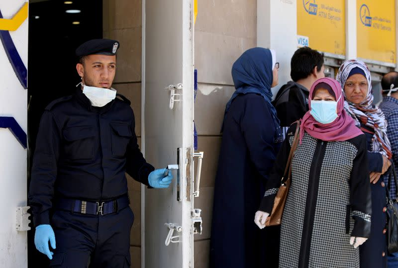 FILE PHOTO: Palestinian policeman stands guard as a woman wearing a mask waits with other people outside a bank to withdraw cash, in Gaza City