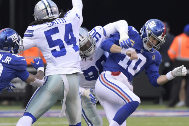 New York Giants quarterback Eli Manning, right, is hit by Dallas Cowboys' Demarcus Lawrence during the first half of an NFL football game, Sunday, Dec. 30, 2018, in East Rutherford, N.J. (AP Photo/Bill Kostroun)