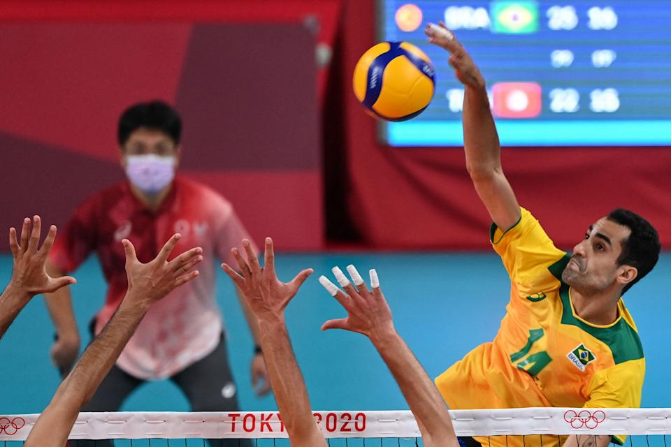 Brazil's Douglas Correia de Souza spikes the ball in the men's preliminary round pool B volleyball match between Brazil and Tunisia during the Tokyo 2020 Olympic Games at Ariake Arena in Tokyo on July 24, 2021. (Photo by YURI CORTEZ / AFP) (Photo by YURI CORTEZ/AFP via Getty Images)