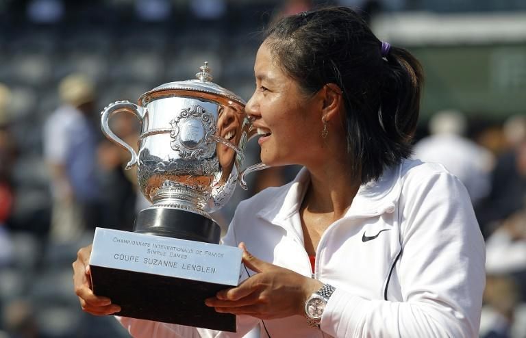 China's Li Na kisses the trophy after winning the 2011 French Open but a decade on she cuts a muted figure in China and has stopped posting on social media