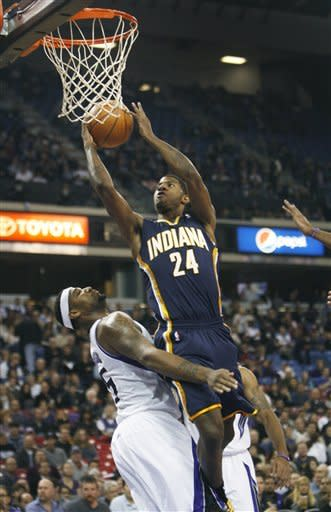 Indiana Pacers guard Paul George (24) drives to the basket against Sacramento Kings defender DeMarcus Cousins during the first half of an NBA basketball game in Sacramento, Calif., on Wednesday, Jan. 18, 2012. (AP Photo/Steve Yeater)