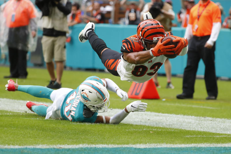 Cincinnati Bengals wide receiver Tyler Boyd (83) stretched for a touchdown as Miami Dolphins defensive back Nik Needham (40) is unable to defend, during the second half at an NFL football game, Sunday, Dec. 22, 2019, in Miami Gardens, Fla. (AP Photo/Wilfredo Lee)