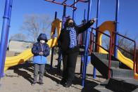Angel, 6, and his mother Angelica Rodriguez walk in a playground in front of their house on Wednesday, Dec. 23, 2020, in Santa Fe, N.M. Rodriguez pointed to a park that's closed due to virus restrictions. Rodriguez and her husband, both cooks, struggled to pay rent this year as their hours were cut in half. (AP Photo/Cedar Attanasio)