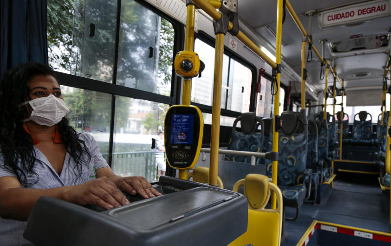 SAO PAULO, BRAZIL - MARCH 17: A bus ticket collector wearing a face mask in the empty bus on March 17, 2020 in Sao Paulo, Brazil. Earlier today, Brazil Health minister Luiz Henrique Mandetta confirmed a first decease related to COVID-19; there are 291 positive cases in the country. (Photo by Miguel Schincariol/Getty Images)