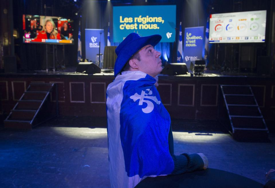 A Bloc Quebecois supporter keeps an eye on the screens as results on federal election night in Montreal, Monday, October 21, 2019. THE CANADIAN PRESS/Graham Hughes