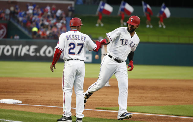 Texas Rangers right fielder Nomar Mazara, right, is congratulated by third base coach Tony Beasley (27) after hitting a solo home run against the Houston Astros during the second inning of a baseball game Friday, March 30, 2018, in Arlington, Texas. (AP Photo/Michael Ainsworth)