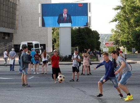 Soccer Football - World Cup - Group A - Russia vs Saudi Arabia - Luhansk, Ukraine - June 14, 2018 Youths play with a ball as Russian President Vladimir Putin is seen on a screen delivering a speech before the match. REUTERS/Alexander Ermochenko