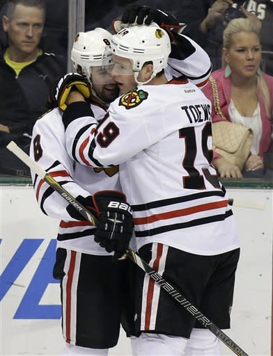 Chicago Blackhawks center Jonathan Toews (19) celebrates his goal with teammate Nick Leddy (8) during the first period of an NHL hockey game against the Dallas Stars, Saturday, March 16, 2013, in Dallas. (AP Photo/LM Otero)