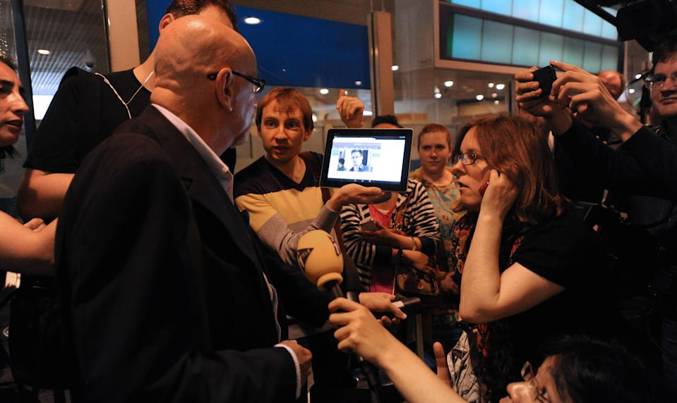 A journalist shows a picture of Edward Snowden to airline passenger at the arrival gate of the Sheremetyevo International Airport in Moscow. (Photo: Asily Maximov/AFP/Getty Images)