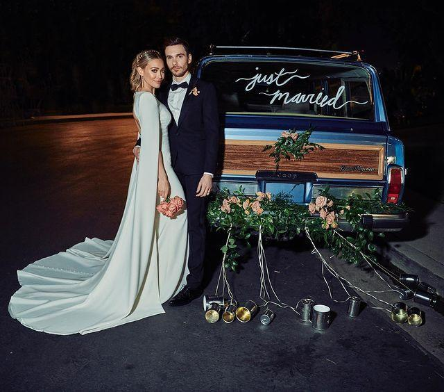 """<p>The actress has shared the first image from her wedding to Matthew Koma and we're pretty obsessed with her bridal gown.</p><p>The 32-year-old wore an ivory-crepe Jenny Packham backless and cape-sleeved gown with exaggerated shoulders for the occasion, while her husband donned a Celine tuxedo.</p><p>'This,' the Californian star captioned the photograph of her and her husband, in which they stand by a car with the words 'just married' written on the back window.</p><p>The <a href=""""https://www.elle.com/uk/life-and-culture/culture/a29586206/lizzie-mcguire-reboot-series/"""" rel=""""nofollow noopener"""" target=""""_blank"""" data-ylk=""""slk:Lizzie McGuire"""" class=""""link rapid-noclick-resp"""">Lizzie McGuire</a> star accessorised her look with a pair of drop earrings and a pearl-encrusted headband. </p><p><a href=""""https://www.instagram.com/p/B6Zh_Ymp31v/"""" rel=""""nofollow noopener"""" target=""""_blank"""" data-ylk=""""slk:See the original post on Instagram"""" class=""""link rapid-noclick-resp"""">See the original post on Instagram</a></p>"""