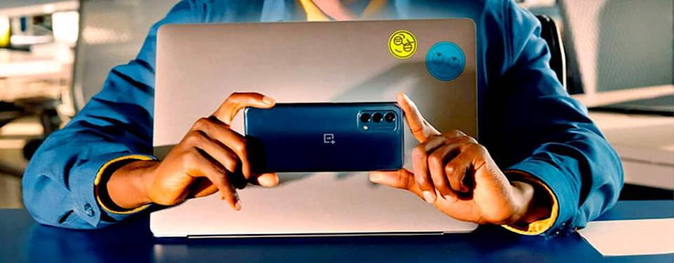 hands holding phone oneplus Nord N200 5G in front of laptop inbody