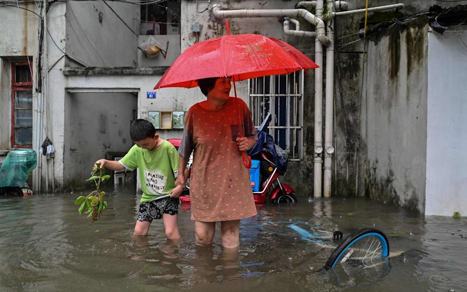 A woman and a boy wade in a flooded street in a neighbourhood in Ningbo, eastern China's Zhejiang province, as Typhoon In-Fa lashes the eastern coast of China - AFP