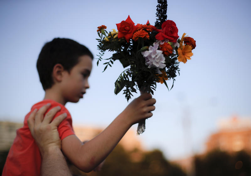 A child holds flowers outside the government headquarters in memory of a 15 year-old girl, raped and killed in southern Romania, after police took 19 hours from the moment she called the country's emergency hotline to intervene, in Bucharest, Romania, Saturday, July 27, 2019. Thousands of people took part Saturday evening in Bucharest in a march protesting the handling of the case, blaming Romanian officials for negligence, incompetence and a lack of empathy. (AP Photo/Vadim Ghirda)
