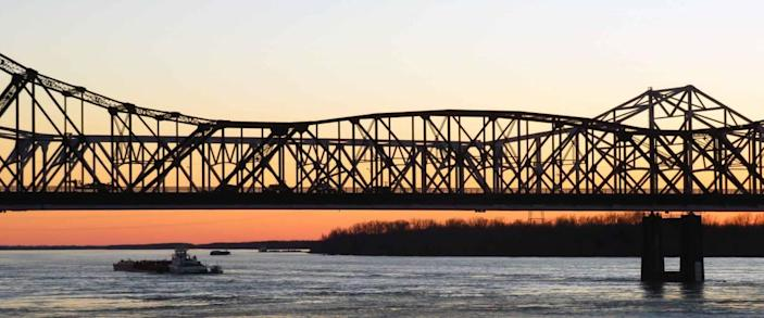 A steel bridge spans the Mississippi River at sunset in Vicksburg, Mississippi.