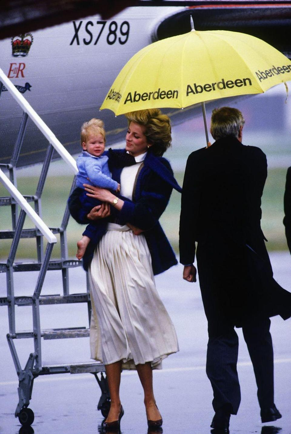 <p>A man sort of, not really protects Princess Diana and Prince Harry from the elements.<br></p>