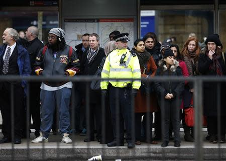 A police officer helps commuters to board buses during London Underground strikes at Kings Cross underground station in London February 6, 2014. REUTERS/Olivia Harris