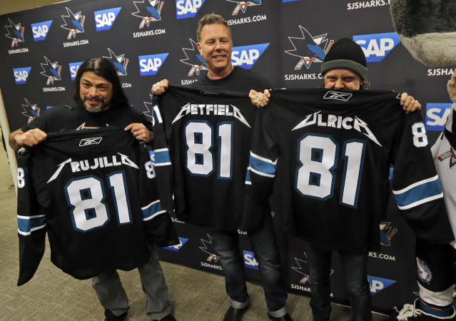Metallica members, from left, Robert Trujillo, James Hetfield and Lars Ulrich pose with San Jose Sharks jerseys before an NHL hockey game against the Los Angeles Kings Wednesday, Jan. 21, 2015, in San Jose, Calif. (AP Photo/Marcio Jose Sanchez)