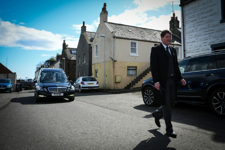 A funeral director leads the hearse carrying the coffin of care worker Janet Livingston, who died of COVID-19, through her home village of Ferryden in Scotland (AFP Photo/Andy Buchanan)