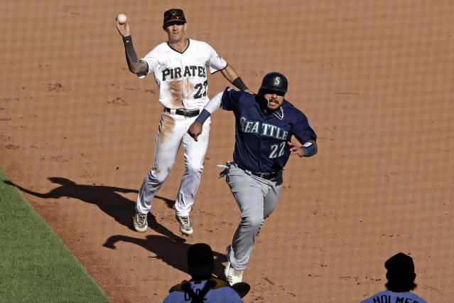 Pittsburgh Pirates shortstop Kevin Newman, left, runs down Seattle Mariners' Omar Narvaez (22) between second and first, completing an inning-ending double play on a ball hit by Austin Nola during the 11th inning of a baseball game in Pittsburgh, Thursday, Sept. 19, 2019. (AP Photo/Gene J. Puskar)